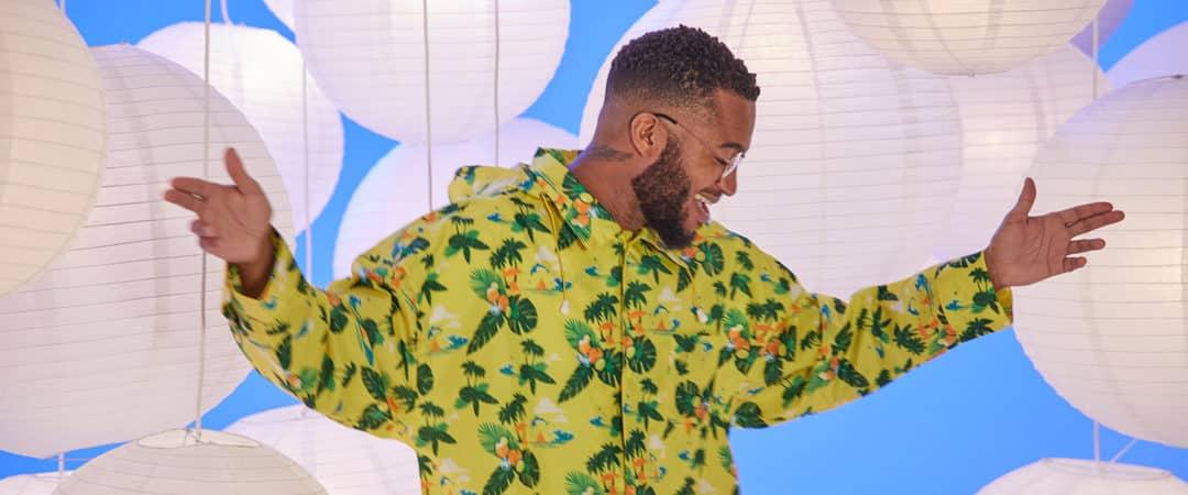 Lachende Jonge man met bril en baardje die danst in een regenshirt Smart Event Managers