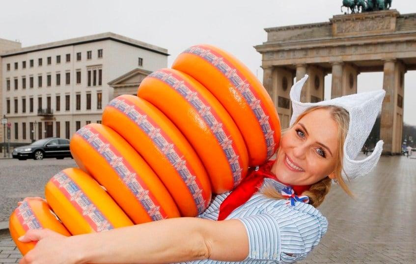 Antje in oud Hollandse klederdracht op een plein in Berlijn met zes grote Kaas in haar handen Smart Event Managers